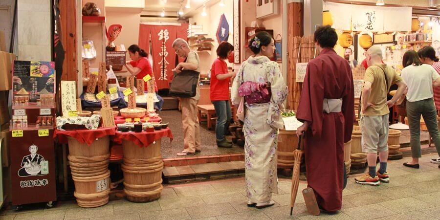錦市場で京都観光のお土産選びをするカップル